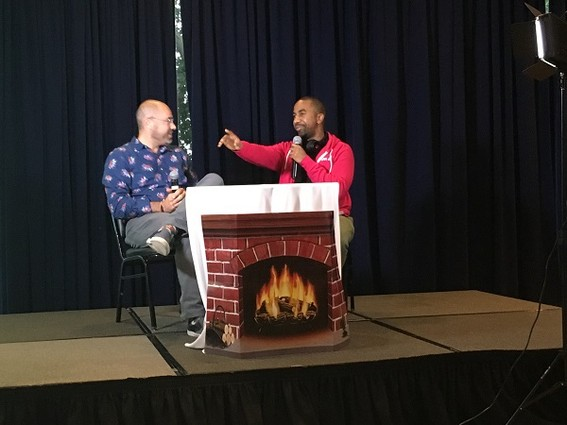 """Photo: The """"Fireside Chats"""" with Aaron Price at the NJ Tech Meetup often become animated as founders talk about their passion for their businesses. Here we see Ali Abdullah, CEO of Newark startup ClaimIt!, making a point. We also like the fake cardboard fireplace! Photo Credit: Esther Surden"""