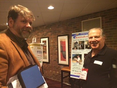 Photo: Mark Annett talks to exhibitor Andrew Hines of Screen Suspender. Photo Credit: Esther Surden