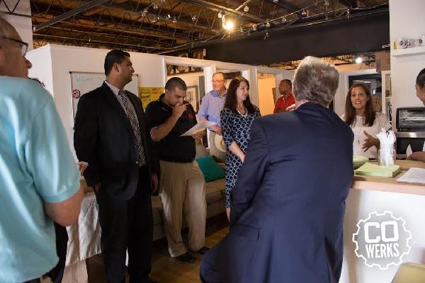 Photo: Pallone (back to camera) talks to entrepreneurs at Cowerks. Photo Credit: Gregory Edgerton @HumbleHumans