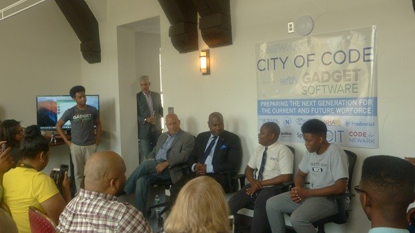 Photo: Panel at the community meeting at Gadget Software including L-R Dan Crain, Mayor Ras J. Baraka and two students who had learned coding through the city program. Photo Credit: Courtesy Gadget Software