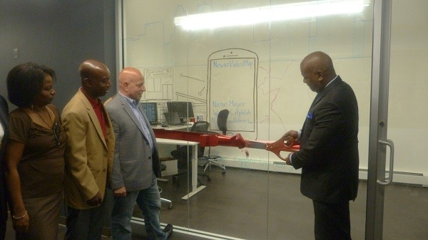 Photo: Newark Mayor Ras J. Baraka (R) cuts the ceremonial ribbon at Gadget Software with CEO Dan Crain, COO Maxwell Riggsbee and Allison Durham, executive manager of the Newark Housing Authority. Photo Credit: Courtesy Gadget Software