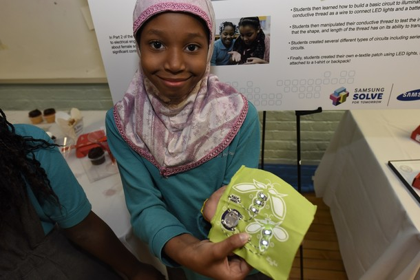 Photo:  Rakayiah Boykin shows off her interactive pocket square, where she sewed a design that lights up with the help of an Arduino computer.  Photo Credit: Courtesy Samsung