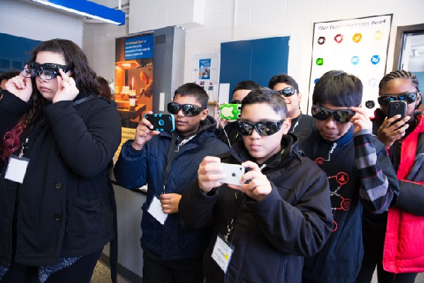 Photo: Students don protective glasses to watch glass-making experiment. Photo Credit: Malcolm Brown for Verizon