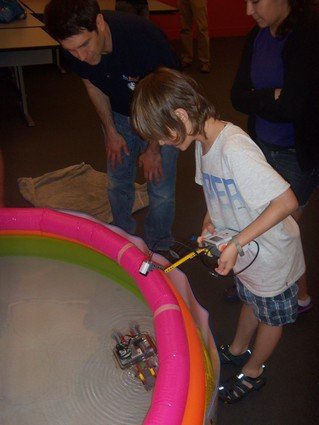 Photo: Students at the Stevens WaterBotics camp test their Lego robot in an inflatable pool. Photo Credit: Alan Skontra