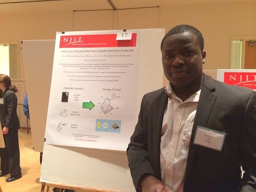 Photo: NJIT's Ronald Forson with his poster about a solar powered wireless charger. Photo Credit: Esther Surden
